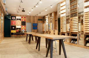 Photograph of solid antique heartpine shelving and tables, mirrors, and integrated lighting produced by Townsend Design for Warby Parker's NYC Meatpacking District retail store project.